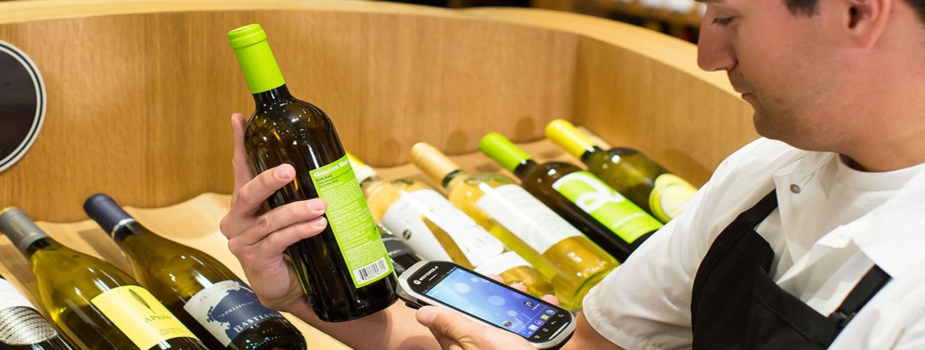 Employee scanning bottle of wine with mobile computer